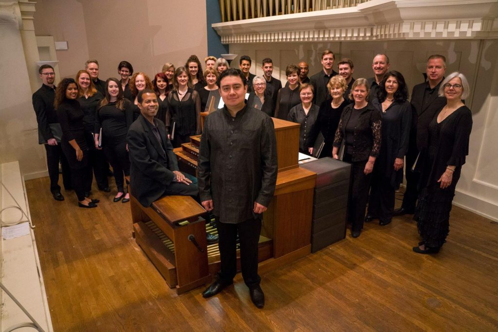 All Souls Choir in the Choir loft with Alejandro Hernandez-Valdez, Director standing and Trent Johnson, Assistant Director, at the organ